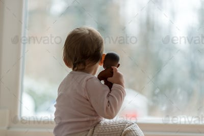 Little baby girl hugging a toy watching the winter snow outdoors
