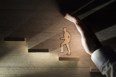 Hand protecting a paper man during progress