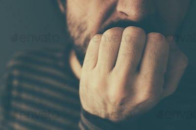 Nervous man bites fingernails