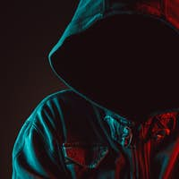 Red and blue lit low key portrait of hooded person