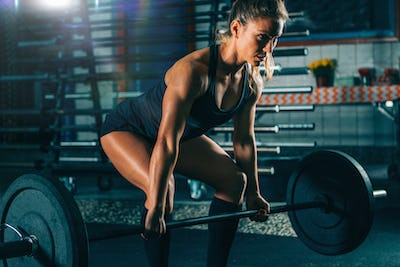Cross training. Female athlete lifting heavy barbells