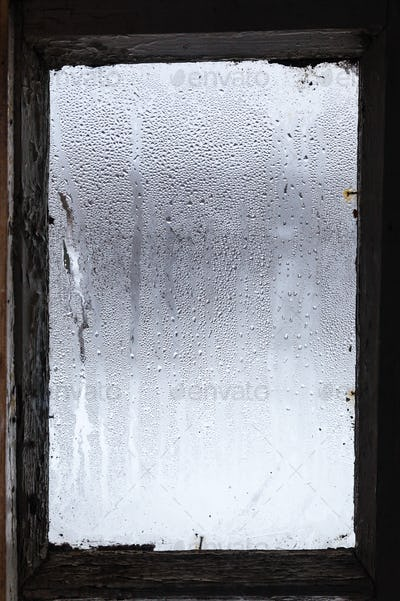 water from melting ice on surface of misted window