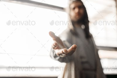 Jesus Christ in white robe reaching out his hand