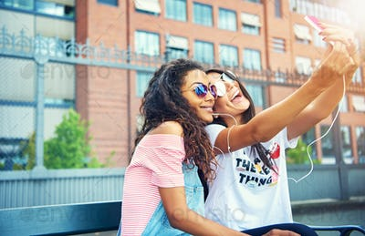 Cute young friends taking selfies near building