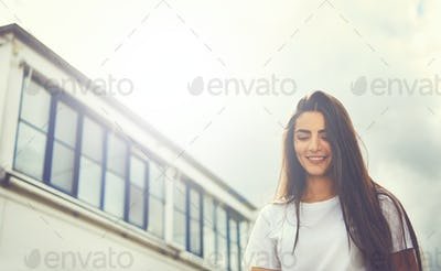 Young woman walking past building