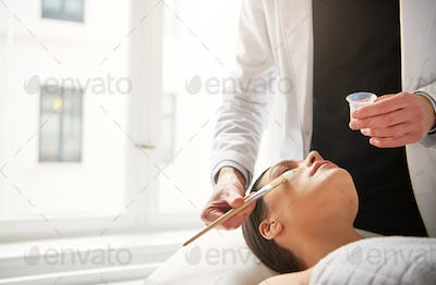 Woman lying with eyes closed during beautician putting mask