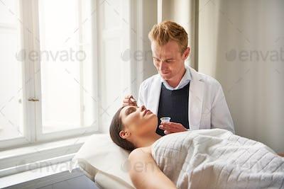 Beautician man applying facial mask to woman face