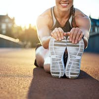 Woman athlete grabs her shoes as she stretches