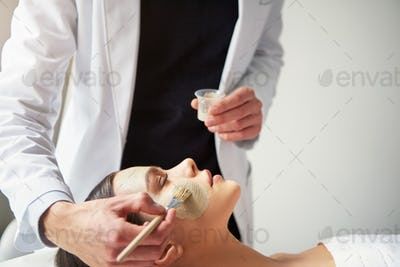 Beautician putting mask on young female face with brush