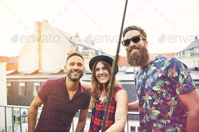 Woman and two male friends stand on patio