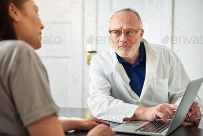 Medical specialist showing laptop to female patient