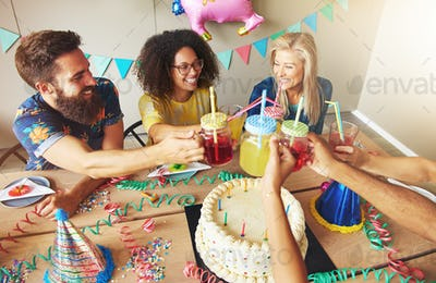 Happy friends holding drinks over cake