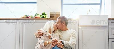 Elderly couple kissing on a kitchen floor