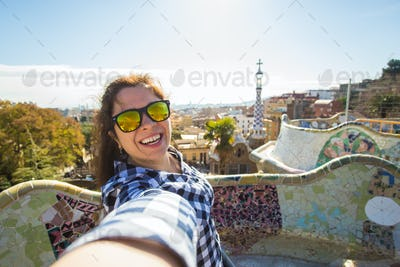 Young woman making selfie in Park Guell, Barcelona, Spain.
