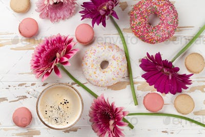 Coffee cup, donuts and gerbera flowers