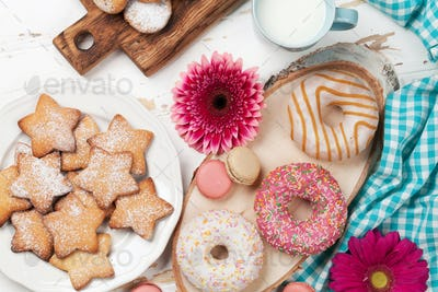 Milk, donuts and flowers on wooden table