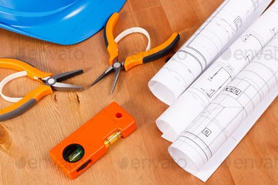 Electrical drawings, protective blue helmet and orange work tools for engineer jobs lying on desk
