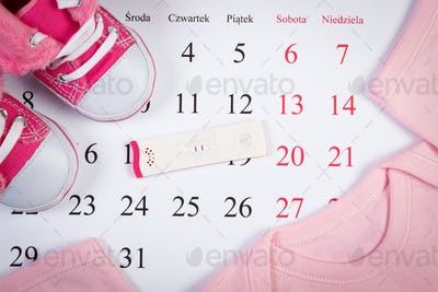Pregnancy test with positive result and clothing for newborn on calendar