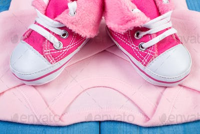 Shoes and bodysuits for newborn, expecting for baby concept