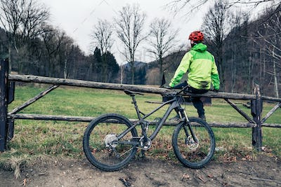 Mountain biker cycling on trail in woods