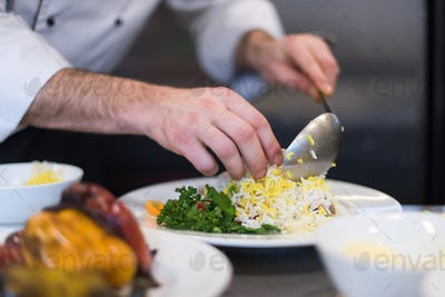 Chef hands serving vegetable risotto