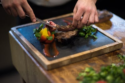 closeup of Chef hands serving beef steak