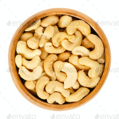Roasted salted whole cashews in wooden bowl over white