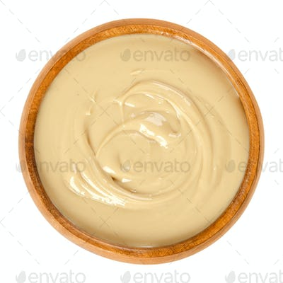 Cashew butter in wooden bowl over white