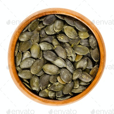 Roasted salted pepita pumpkin seeds in wooden bowl over white