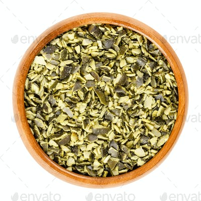 Roughly chopped raw pepita pumpkin seeds in wooden bowl over white