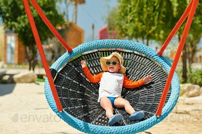 Toddler child swinging on beach