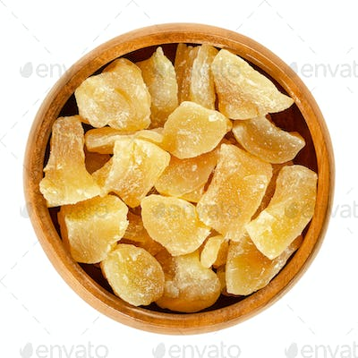 Candied ginger root chunks in wooden bowl over white