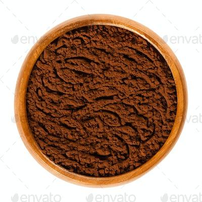 Fine cocoa powder in wooden bowl over white