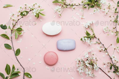Different soaps bar on pink with spring flowers