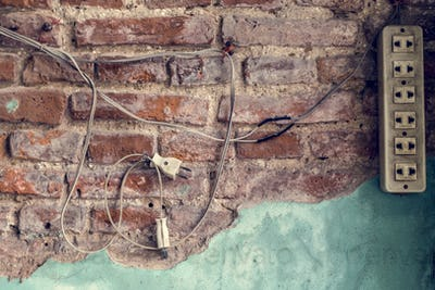 Power plug hanging on a brick wall