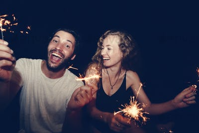 Happy couple with sparklers in the night