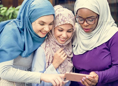 Islamic women friends looking at smart phone with smiling