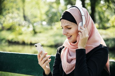 Islamic woman using mobile phone to listening music