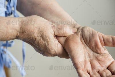 Closeup of elderly hands checking pulse