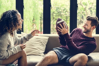 Young couple watching american football at home