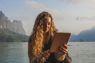 Woman using her tablet by a lake