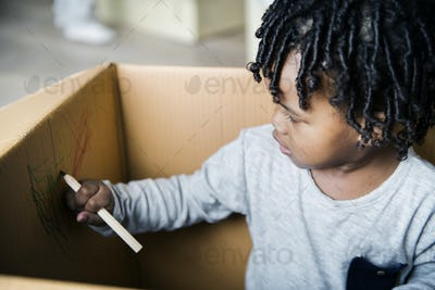 Young black boy drawing in a box