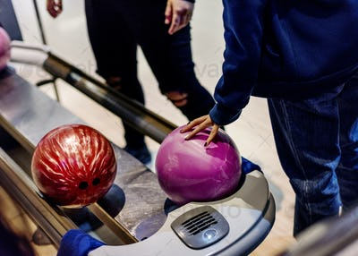 Girl picking up a bowling ball hobby and leisure concept