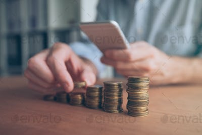 Businessman using smartphone with stacked coins in foreground