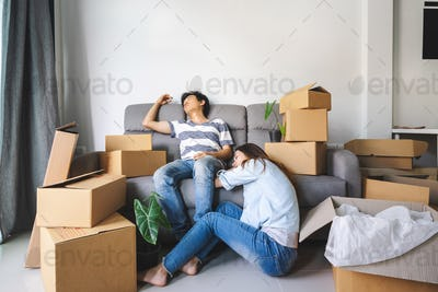 Young tried couple moving in new home, sitting and relaxing on sofa with cardboard boxes