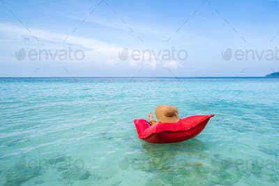 Young woman relaxing and enjoying with float mattress at the tropical beach