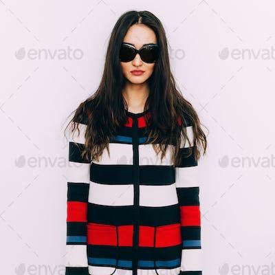 Brunette model in fashion striped coat and stylish sunglasses. S