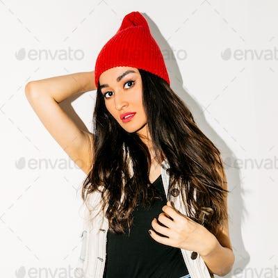 Brunette Pretty girl in fashion beanie cap. Urban style