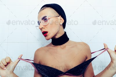 Sexy model in fashion Tomboy Look. Stylish glasses, choker and b