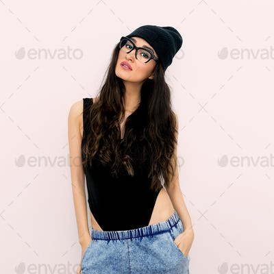 Stylish brunette in black body and beanie cap. Jeans. Tomboy sty